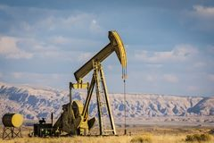 Oil Well With Sky Background. Oil Well In High Desert Landscape Blue Sky Background Stock Photos