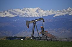 Oil Well pump jack and Snow Capped Peaks Royalty Free Stock Photo