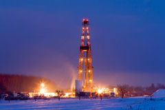 Oil well in the snowy landscape lit up at night. Royalty Free Stock Photos