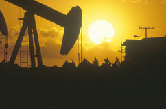 Oil Well at sunset. Oil drilling well silhouetted at sunset Stock Photo