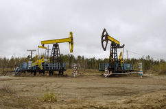 An oil well with a swinging rod pumping. Pumping unit - Individual mechanical actuator rod pump Royalty Free Stock Photography