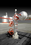 OIL WELL WELLHEAD. Silver Oil Well Wellhead Against Oil Storage Tanks stock photos