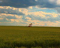 Oil well in the wheat in Western Kansas Stock Images