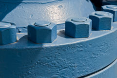 Oil wellhead bolts. Oil wellhead with large nuts and bolts.  The wellhead provides pressure containment for the oil well Stock Photography