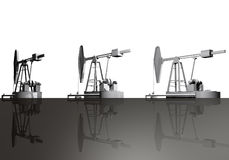 Oil wells. Three oil wells on a black surface Stock Images