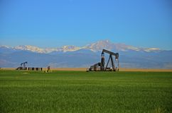 Oil Wells, Pump Jack , corn field and Mountains