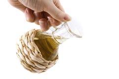 Oil in a wicker bottle Stock Photo