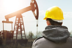 Oil worker. In yellow helmet on of background the pump jack Royalty Free Stock Photo