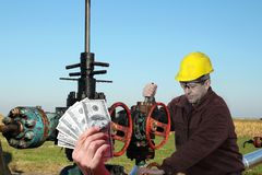 Oil Worker in Action at Oil Well Make Money as a Concept stock photography