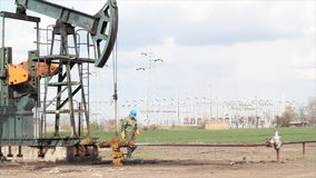 Oil worker check pump jack stock video footage