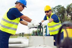 Oil worker closes the valve on the oil pipeline royalty free stock images