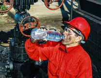 Oil Worker Drinks Water Beside Oil Well Stock Photo