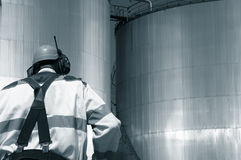 Oil worker and fuel tanks Stock Images