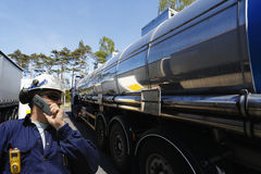 Oil worker and fuel trucking royalty free stock image
