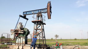 Oil worker on oilfield. Oil worker climbs up to the pump jack stock footage