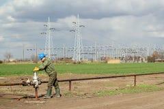 Oil worker open pipeline valve Royalty Free Stock Image