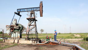 Oil worker and pump jack. Oil worker check pump jack stock footage