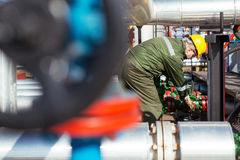Oil worker repairing wellhead valve with the wrench Stock Images