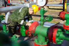 Oil worker repairing wellhead valve with the wrench Royalty Free Stock Images