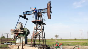 Oil worker. Standing on pump jack stock video