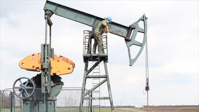 Oil worker. Standing at the pump jack stock footage