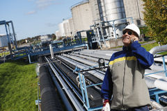 Oil worker talking in phone inside refinery Stock Images