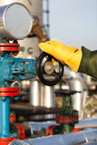 Oil worker turning valve Royalty Free Stock Image