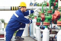 Oil worker is turning valve on the oil pipeline. Young Oil worker is turning valve on the oil pipeline royalty free stock image