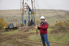 Oil worker in uniform and helmet, with mobile phone. Royalty Free Stock Photos