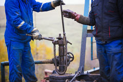 Oil workers check oil pump. Roustabouts doing dirty and dangerous work. On an oil well servicing rig Royalty Free Stock Image