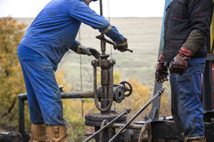 Oil workers check oil pump. Roustabouts doing dirty and dangerous work Stock Photo