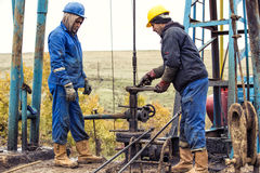 Oil workers check oil pump. Roustabouts doing dirty and dangerous work