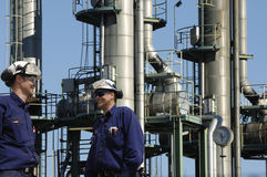 Oil workers in front of oil and fuel towers. Two oil and gas workers, engineers in front of large refinery towers, details inside refinery Stock Photography