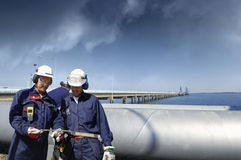 Oil workers with giant main pipeline Royalty Free Stock Photo