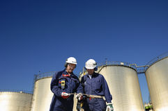 Oil workers and refinery tanks. Two engineers working inside refinery, four large fuel tanks in background Stock Photos