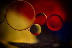 Oildrops rode zwarte geel Stock Foto