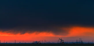 Oilfield with oil pumps and oil rigs profiled on sunset sky. Oilfield with oil pumps and oil rigs profiled on sunset stormy sky in an active oilfield in Europe royalty free stock photo