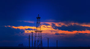 Oilfield with oil rigs profiled on sunset sky. Oilfield with oil pumps and oil rigs profiled on sunset stormy sky in an active oilfield in Europe royalty free stock photo