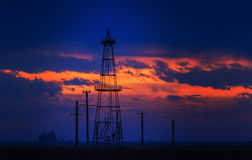Oilfield with oil rigs profiled on sunset sky. Oilfield with oil pumps and oil rigs profiled on sunset stormy sky in an active oilfield in Europe royalty free stock photos