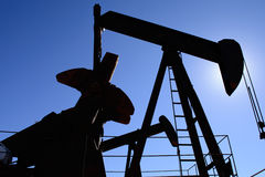 Oilfield pumpjack, rusty and old, silhouetted by the sun. Clear blue sky background Stock Images