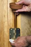 Oiling the hings of a door using an oil can stock photography