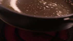 Oiling hot pan. Pouring oil into frying pan - ready for frying. Oiling hot pan - close-up on top of a kitchen tile hot stock footage