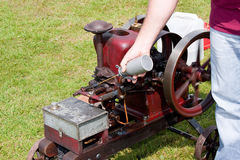 Oiling Vintage Red Stationary Engine with Spin Royalty Free Stock Image