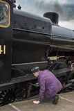 Oiling the wheels. SHEFFIELD PARK, UK - MARCH 19, 2016: Train worker oils the wheels of a steam engine Royalty Free Stock Photography