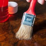 Oiling a wood table with a brush. Applying oil on a wood table with a brush Royalty Free Stock Photo