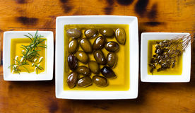 Oilive oil with olives and herbs on wooden background Stock Image