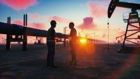 Oilman y hombre de negocios que hablan cerca de la tubería en una puesta del sol en el fondo de las bombas de aceite Cinemático r libre illustration