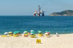 An oilrig looms over a beach near Rio de Janiero. An oil rig is visible in the sea near a beach at Niteroi, outside Rio de Janiero. Brazil found huge oil stock image