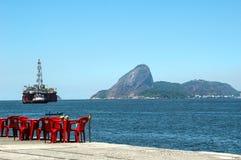 An oilrig looms over a beach near Rio de Janiero Royalty Free Stock Photo