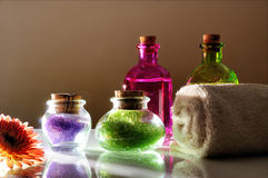 Oils and bath salts on white glass table dimly light Stock Photos